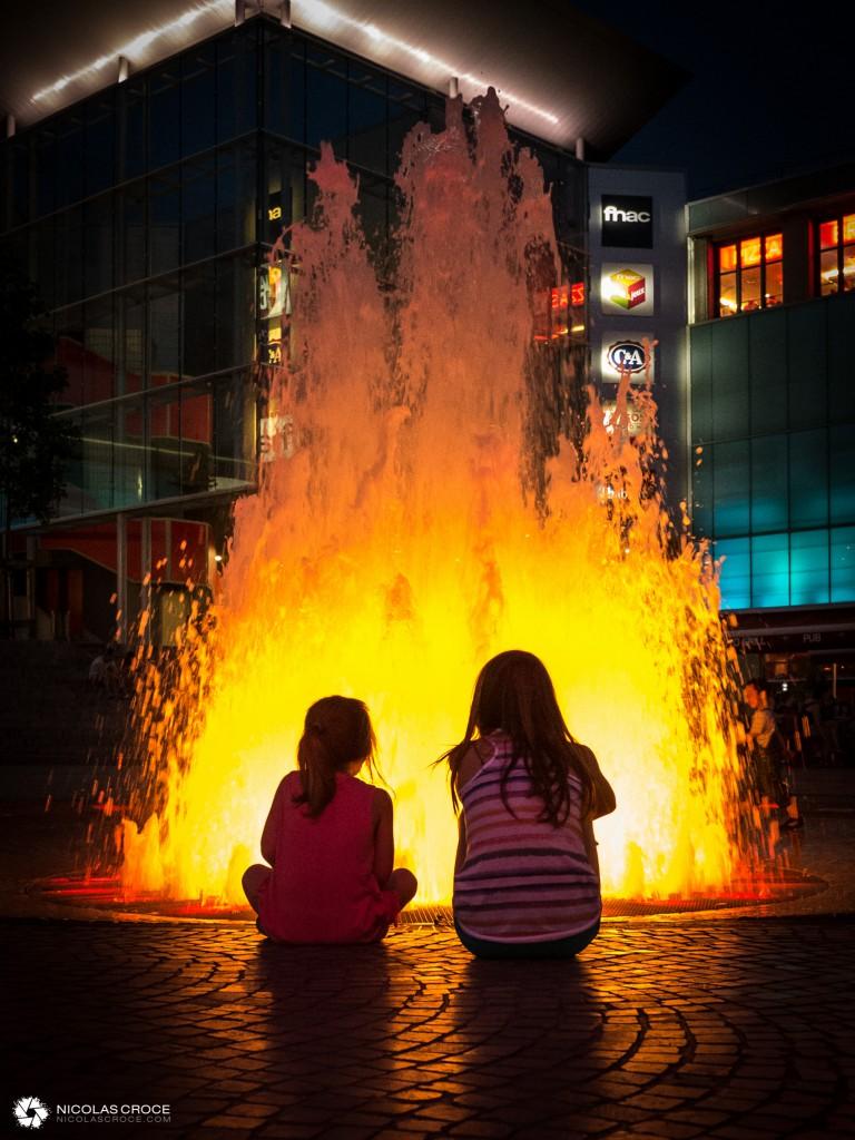 Des enfants regardent la fontaine de la place de Jaude, qui simule un volcan en éruption